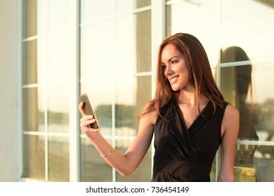 beautiful young woman in black dress making selfies
