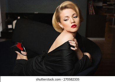 Beautiful young woman in black evening dress lying on sofa