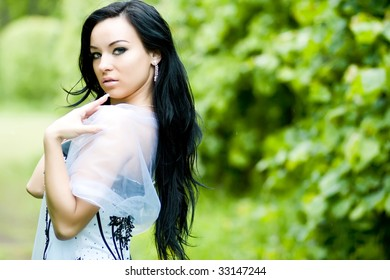 Beautiful young woman with black hair in summer park