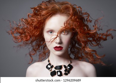 Beautiful young woman with black jewelry and red-hair on grey background. Nude pretty lady with bright red lipsstick and modern art makeup. Sensual model pose in photo-studio. Sexy naked body.