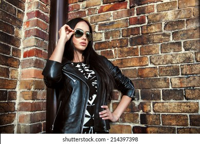 Beautiful young woman in black leather jacket and sunglasses posing over brick wall