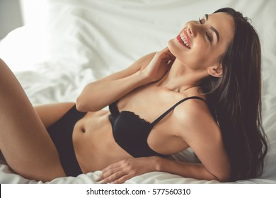 Beautiful young woman in black lingerie is smiling while lying on bed