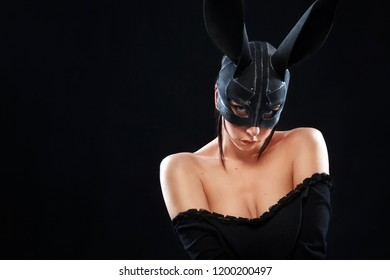 Beautiful young woman in black mysterious halloween mask - headpiece. Female in bdsm black fetish rabbit mask. Fashion photo.