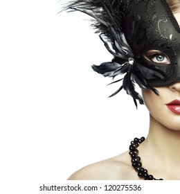 Beautiful young woman in black mysterious venetian mask. Fashion photo