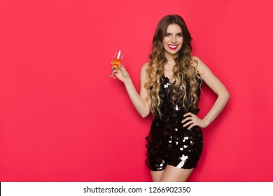 a4e5eaa9b0f5 Beautiful young woman in black sequin jumpsuit is holding glass of wine