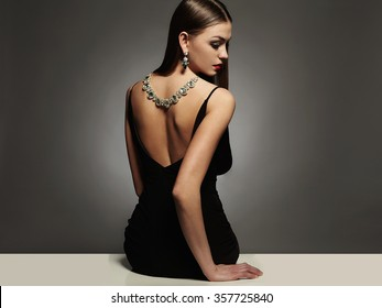 beautiful young woman in a black sexy dress.luxury beauty brunette sitting girl Girl with a necklace on her back