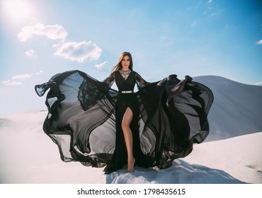 Beautiful young woman in black silk elegant dress. Gorgeous girl, fashion model posing in desert. White sands background, blue sky bright sun. fabric of long skirt flutters in motion flying in wind