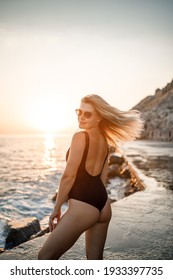 Beautiful young woman in a black swimsuit alone on the beach by the sea at sunset. An adult slender girl resting on the ocean shore at sunset. Summer vacation concept. Selective focus