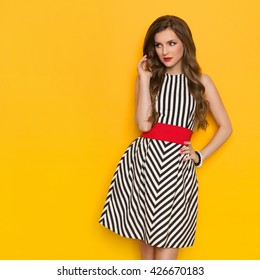 Beautiful young woman in black and white striped dress posing with hand on hip and looking away. Three quarter length studio shot on yellow background.