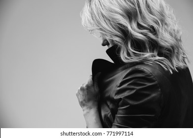 Beautiful young woman with blond hair standing in profile. She holds the collar of her leather jacket with her hand and covers her face. The photo is black and white.