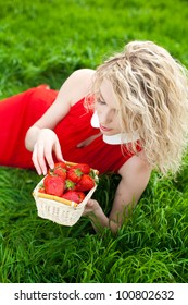 A beautiful young woman, a blonde with a basket of strawberries. Spring, bright green grass. A series of photos in my portfolio