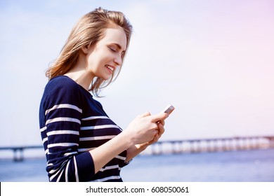 Beautiful young woman, blonde, making reminders outdoors using smartphone app and fast 4G internet connection while standing against river and bridge. Sunny spring day
