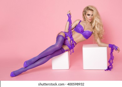 Beautiful young woman blonde model with long legs and hairs dressed in a lilac underwear, lies on the colored blocks on a pink background, has a big breasts and perfect body and firm buttocks