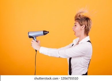 Beautiful young woman with blonde short hair using hairdryer over yellow background.. Hair care. Funny coiffure.