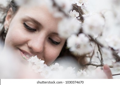 beautiful young woman in blooming cherry blossoms garden.