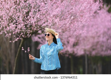 beautiful young woman in blooming cherry blossoms garden