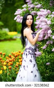 Beautiful young woman in blooming garden