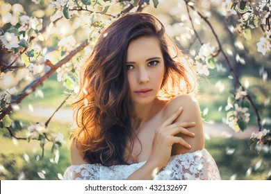 Beautiful young woman with blossom branch, young woman in spring blossom garden