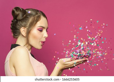Beautiful young woman blowing confetti on bright pink background