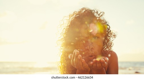 Beautiful young woman blowing glitter on the beach at sunset