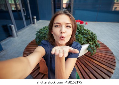 Beautiful young woman is blowing a kiss while posing for a selfie over round bench background in the city
