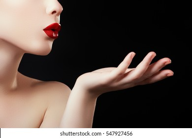 Beautiful young woman blowing a kiss from her hand. Model with perfect dark redl lips and manicured nails