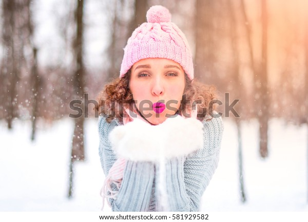 Beautiful young woman is blowing snow from her hands. Magic snowfall effect