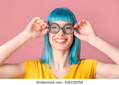 Beautiful young woman with blue color dyed hair and hipster funny goggles smiling in front of pastel studio background.