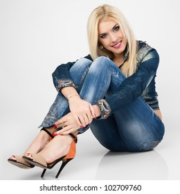 Beautiful young woman in a blue denim suit sit on the floor.