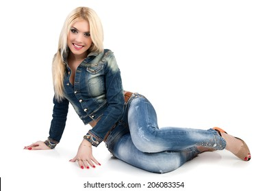 Beautiful young woman in a blue denim suit sit on the floor. Woman isolated on white background.