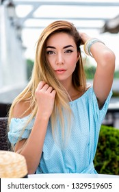 Beautiful and young woman in blue dress. In the summer in cafe at a restaurant table. It corrects hair, emotions of tenderness of pleasure and rest after work. Close-up long hair and casual makeup.