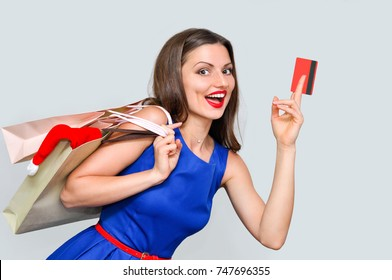 beautiful young woman in blue dress with bags and a credit card for shopping