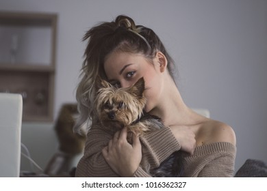 Beautiful young woman with blue eyes posing with her yorkshire dog.