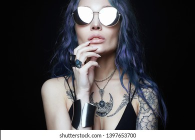 Beautiful young woman with blue hair tattoo. freak style tattooed girl in sunglasses and jewelry