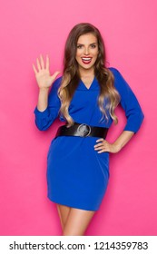 Beautiful young woman in blue mini dress and black belt  is holding hand raised, showing five fingers and talking. Three quarter length studio shot on pink background.