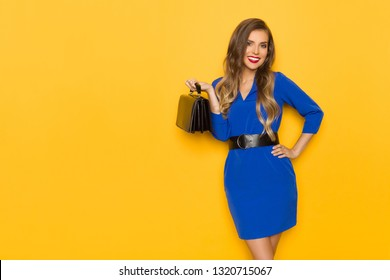 6e73836664ca Beautiful young woman in blue mini dress is holding black leather bag