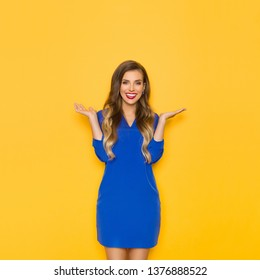 b53f9099a Beautiful young woman in blue mini dress is holding hands raised, looking at  camera and