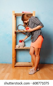 Beautiful young woman in blue room on wooden cupboard background posing with red apple. juggling apples