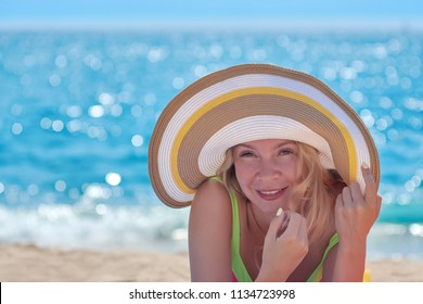 Beautiful young woman in bonnet hat against the sea. She is looking in the camera.
