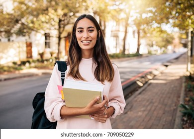 Beautiful young woman with book going to college. Young female university student with book in campus.