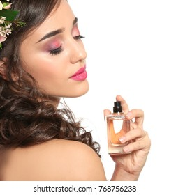 Beautiful young woman with bottle of floral perfume on white background