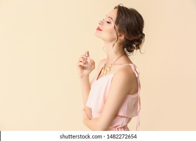 Beautiful young woman with bottle of perfume on light color background