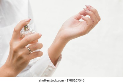 Beautiful young woman with a bottle of perfume on a light background, hands of a girl close-up. Perfumes and aromatherapy. The concept of beauty.