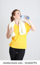 Beautiful young woman with bottle of water and towel