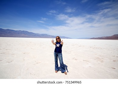 Beautiful young woman with bottle of water in Death Valley, California. Water in desert