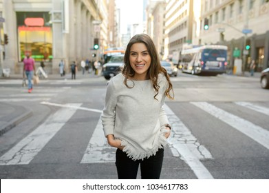 Beautiful young woman at boulevard crosswalk in urban scenery, downtown, at sunset, smiling at camera