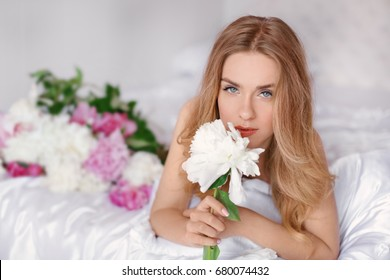 Beautiful young woman with bouquet of peonies on bed at home