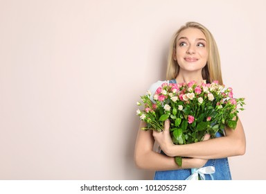 Beautiful young woman with bouquet of roses on color background