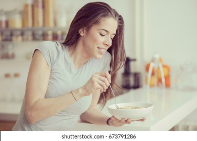 Beautiful young  woman breakfast cereals in the kitchen