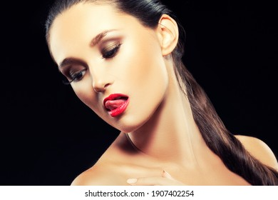 Beautiful young woman with bright eye shadow, lips makeup on dark background, closeup